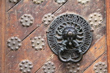 Lion door knocker on ancient wooden door