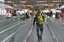 Man with a back bag in an airport on a travelator going to catch a plane to go on a journey
