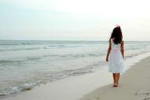 little girl in a dress walking on a beach