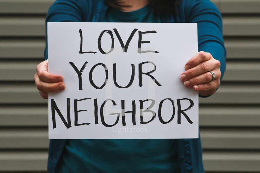 A woman holding up a sign that reads love your neighbor