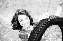 a smiling woman on a tire swing