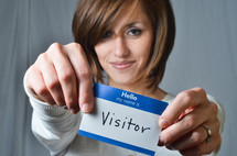 woman holding a name tag that reads visitor