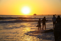 People wading in the ocean at sunset