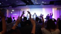 raised hands during a worship service and people on stage