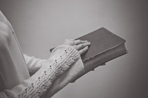 a woman holding a Bible in front of her
