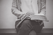 a woman sitting reading a Bible in her lap