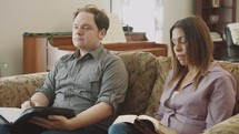 couple sitting on a couch listening to a speaker at a Bible study