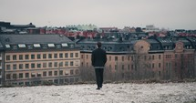 man standing on a hilltop looking out of the rooftops of buildings in a town