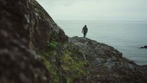 a man walking along a rocky shore