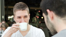 two men in conversation over coffee