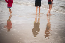 Wading children reflected in the water.