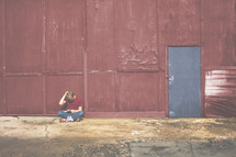 man reading outdoor in front of a red building