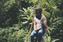a young woman sitting on a rock in a jungle