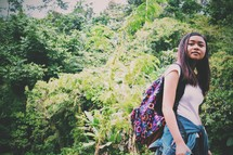 teen girl with a backpack in a jungle