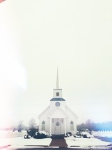 white church and steeple and snow on the ground