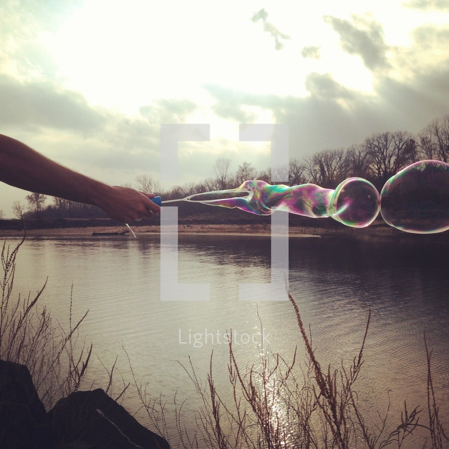 bubbles from a bubble wand over lake water