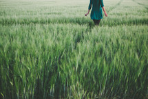 A woman standing in a field of green grass.