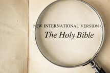 The Holy Bible title page under a magnifying glass