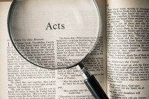 magnifying glass over Bible - Acts
