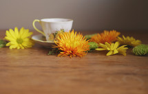 a cup of tea on table with flowers