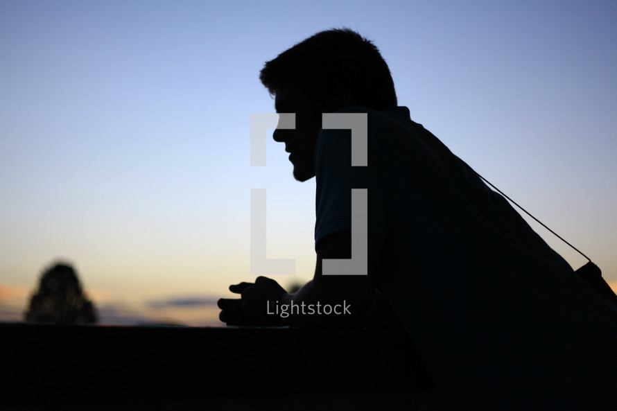 Man leaning on wall at sunset