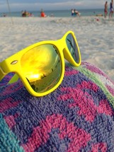 Yellow sunglasses on a beach towel at the beach.
