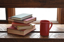 stack of books and a coffee mug