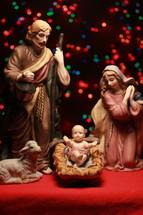 holy family figurines and colorful bokeh Christmas lights