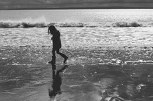 a girl child in rain boots walking on a shore