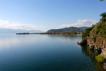 A large lake with clear still water among mountains.