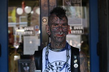 A tattooed man with a mohawk and nose ring.