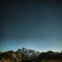 stars in the sky over a rugged mountain peaks