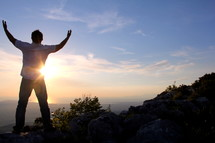 a man with raised hands standing on a mountain top praising God