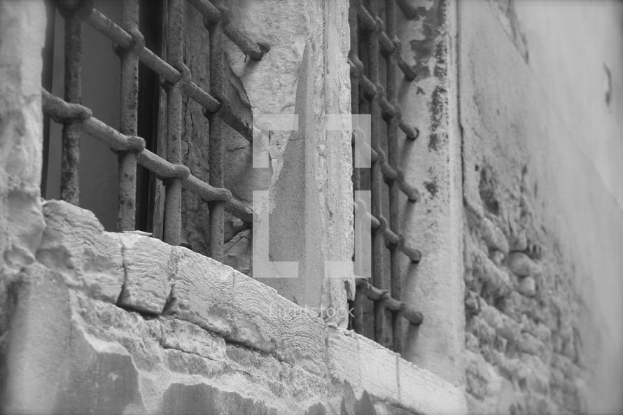 An ancient stone wall with iron bars on the windows.
