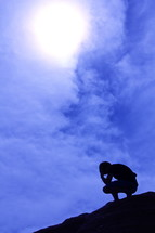 Silhouette of a man kneeling in prayer at the top of a mountain