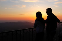 Silhouette of a man and woman looking out toward the sunset.