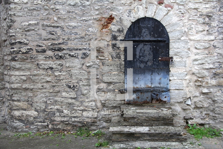 Arched doors in a stone wall doorway