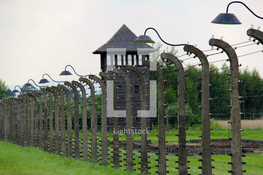 Electric fence, barbed wire and guard towers around concentration camp