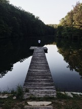 man standing at the end of a dock on a pond