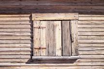 weathered wood shuttered window
