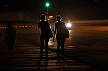 women walking on a sidewalk at night