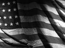 A faded old American flag in black and white.