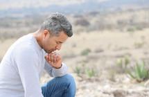 a man kneeling in prayer in a desert