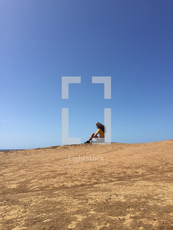 woman sitting at the top of a sand dune