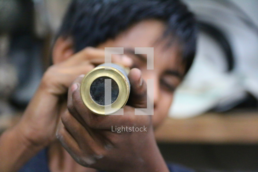 Young boy peers through an old brass telescope