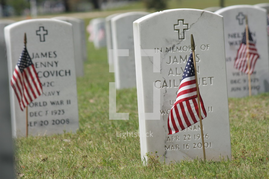 American flags in front of tombstones