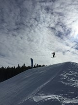 A snow skier flying over a jump.