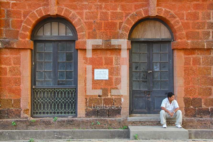 man sitting on a step in front of a brick building