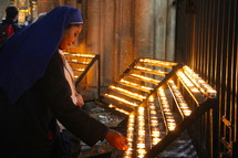Nun lighting votive or prayer candle in Catholic Cathedral.