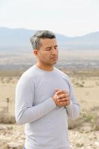 a man praying in a desert
